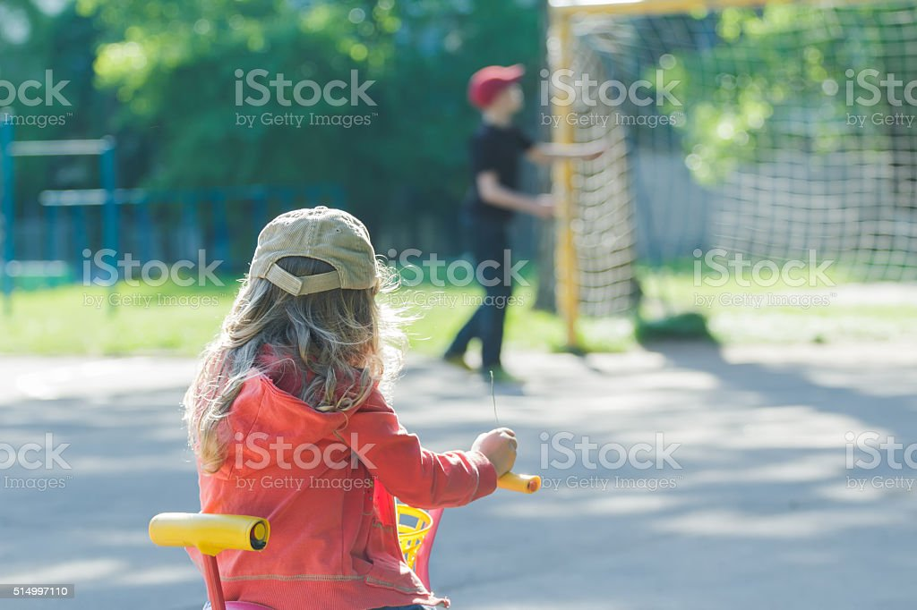 Little girl looking at boy on kids football ground stock photo