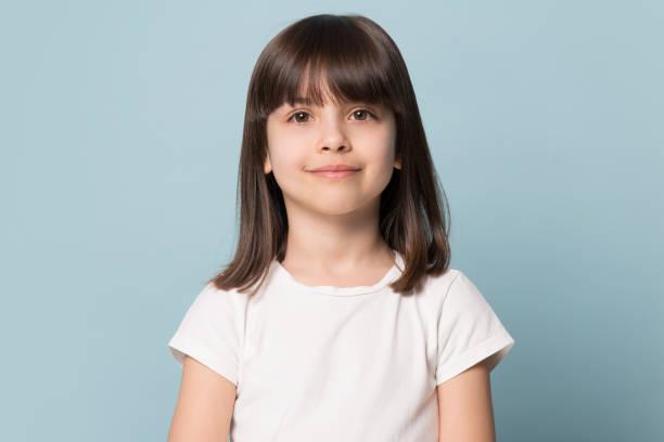 liten flicka tittar på kameran isolerad på blå studio bakgrund - 6 7 år bildbanksfoton och bilder