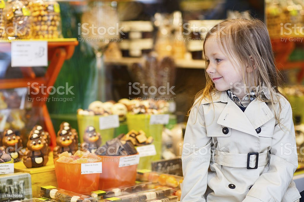 Little girl looking at chocolate in shop stock photo