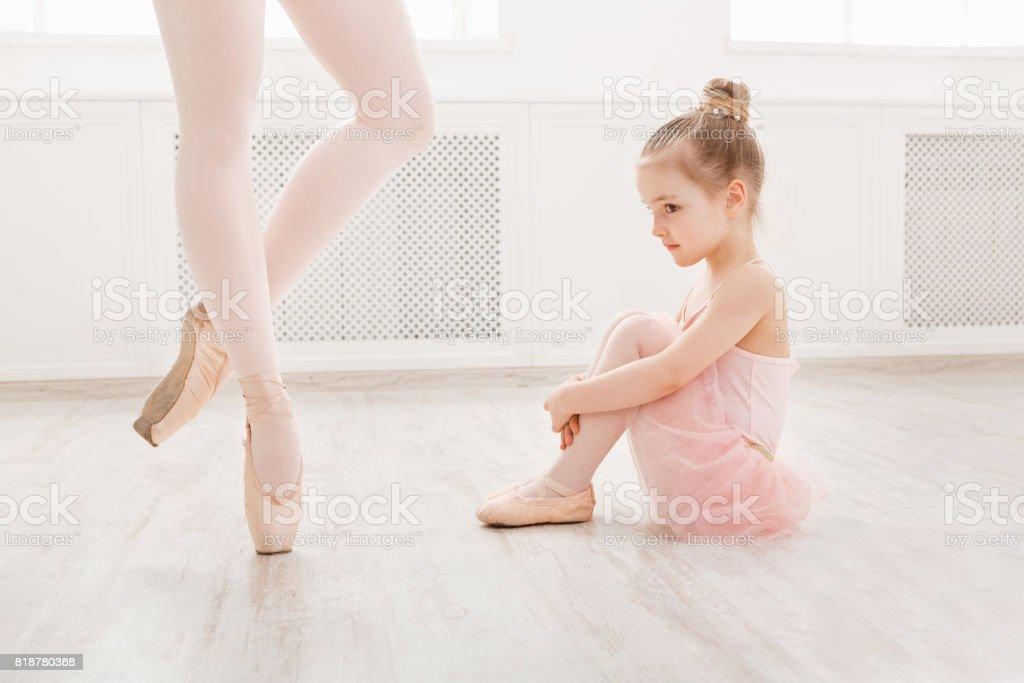 Little girl looking at professional ballet dancer stock photo