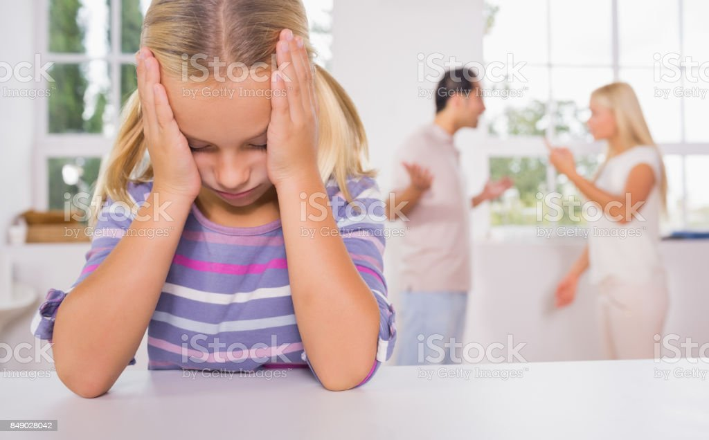 Little girl looking depressed in front of fighting parents stock photo