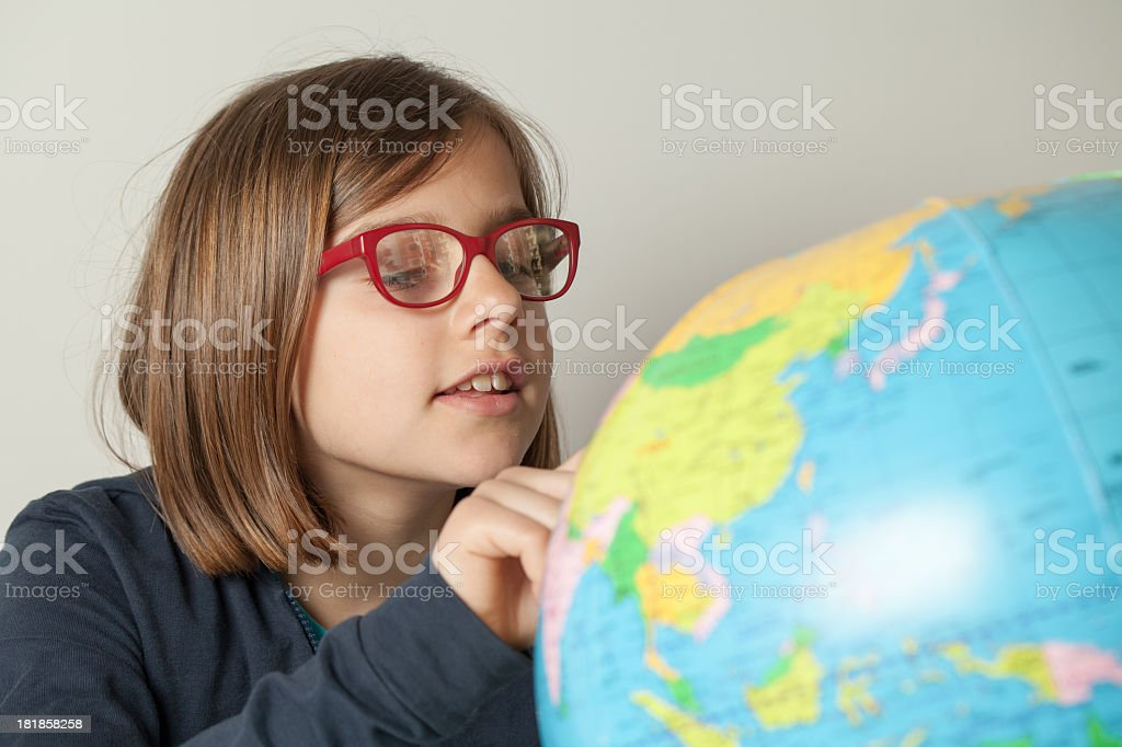Little Girl Looking For a Place on Her Globe stock photo