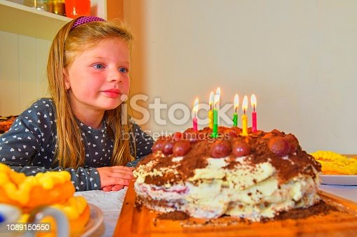 istock Little girl looking on her birthday cake. Small girl celebrating her six birthday. Birthday cake and little girl 1089150550
