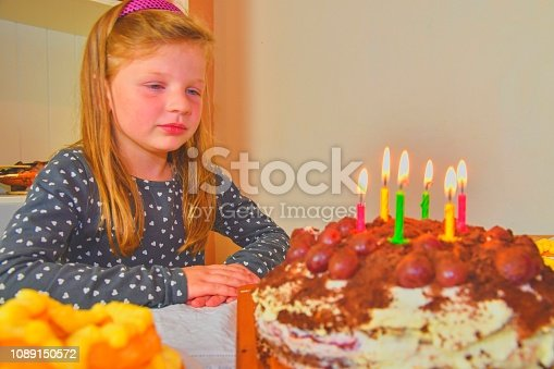 istock Little girl looking on her birthday cake. Small girl celebrating her six birthday. Birthday cake and little girl 1089150572