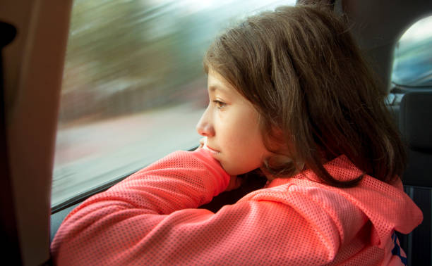 Little girl looking out car window stock photo stock photo