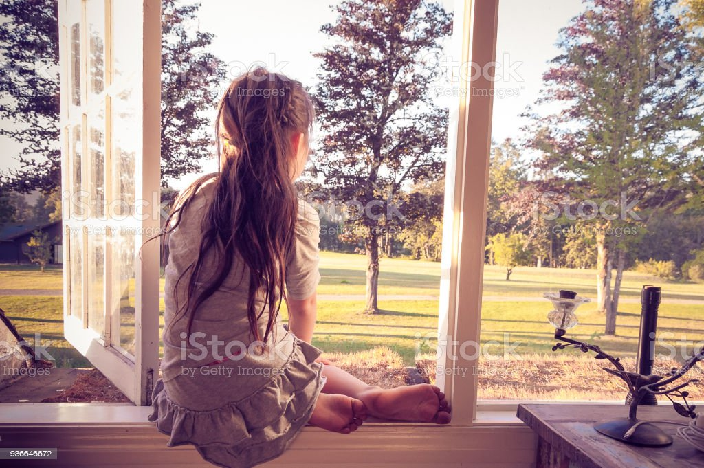 Little girl looking out of her bedroom window alone royalty-free stock photo