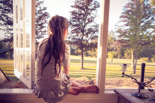 Little girl looking out of her bedroom window alone stock photo