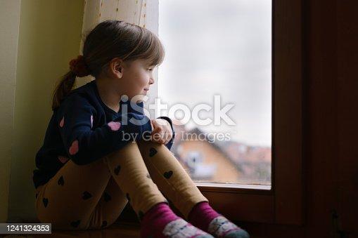 Cute little girl sitting by the window