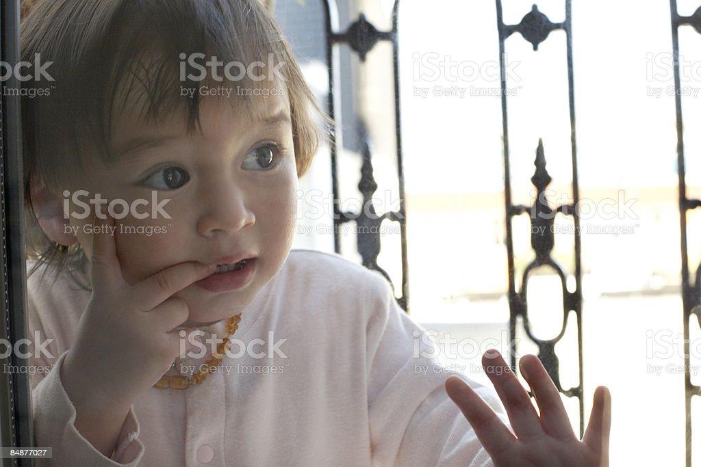 little girl looking threw glass window royalty-free stock photo