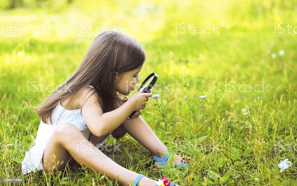 Little girl looking through a magnifying glass on flower royalty-free stock photo