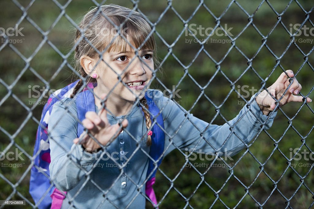 Little girl looking through chain link fence stock photo
