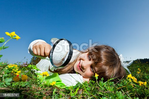 525737167 istock photo Little girl looking through magnifying glass 184923741
