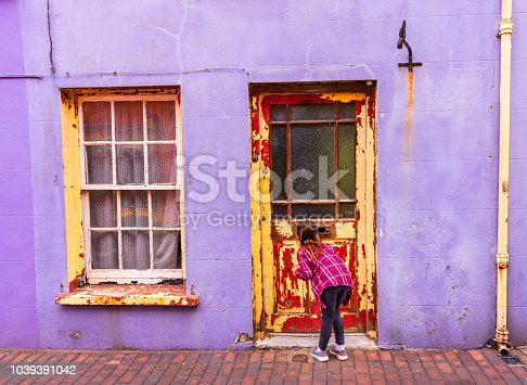 The paint is peeling off the rotten wooden door and window. The colorful scene is part of the rich character of Kinsale, a coastal fishing town in Southern Ireland.