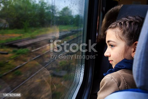 Little girl looking through window with reflections. She travels on a train.Rain drops on the window. Black and white image