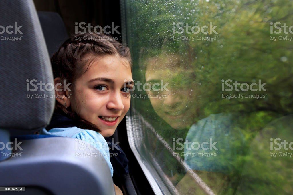Little girl looking through window with reflections. She travels on a...