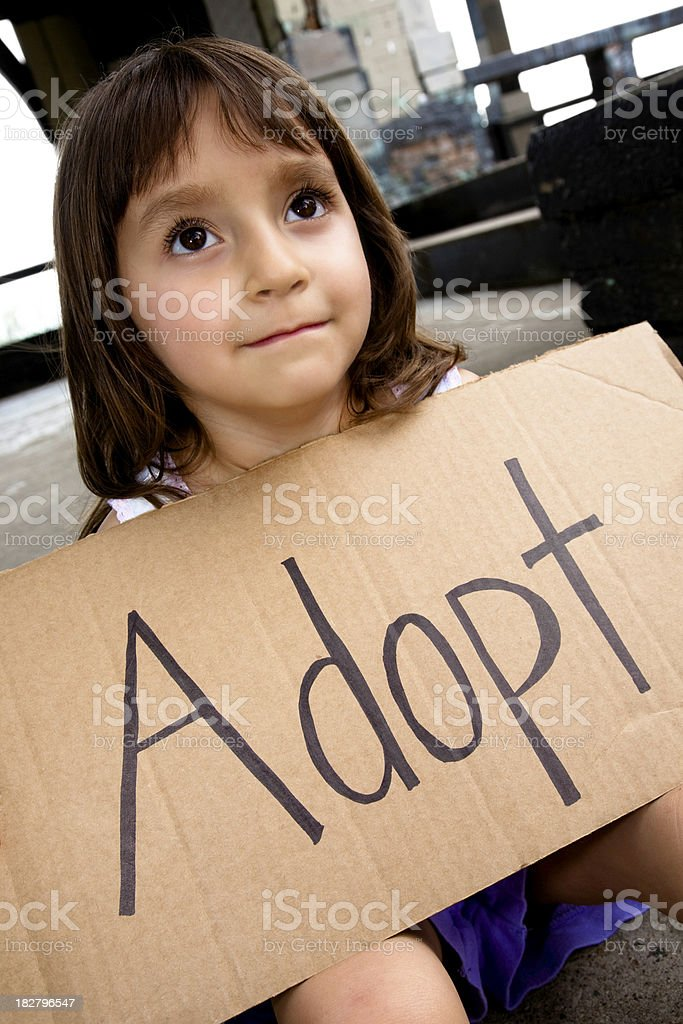 Little Girl Looking Up Holding Adopt Sign royalty-free stock photo