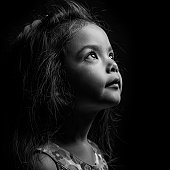 young girl crying. Hands in a gesture of prayer. Black and white portrait