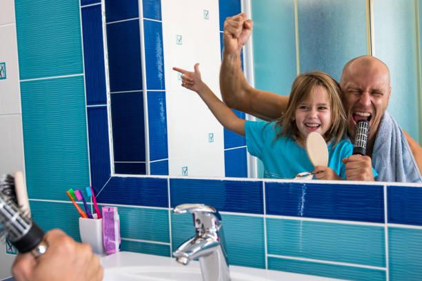 ein kleines mädchen schaut ihr vater in einem spiegel, wie sie das lied singen. - papa humor stock-fotos und bilder