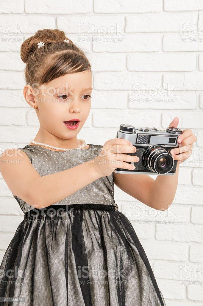 little girl looks at retro camera stock photo
