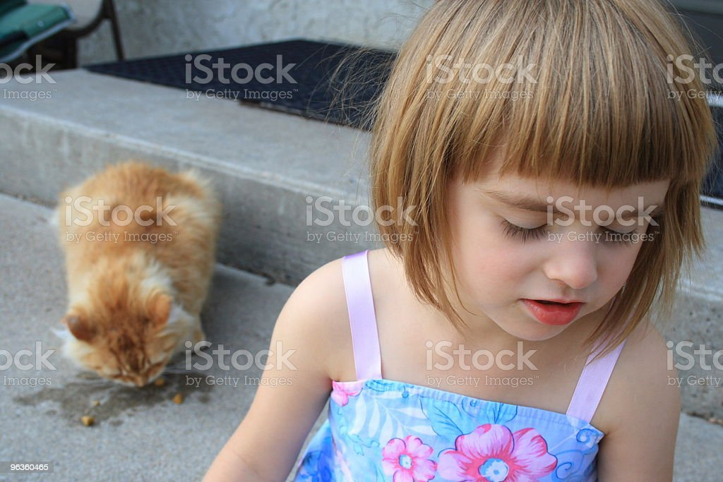 little girl looks away disgusted at cat eating behind her royalty-free stock photo