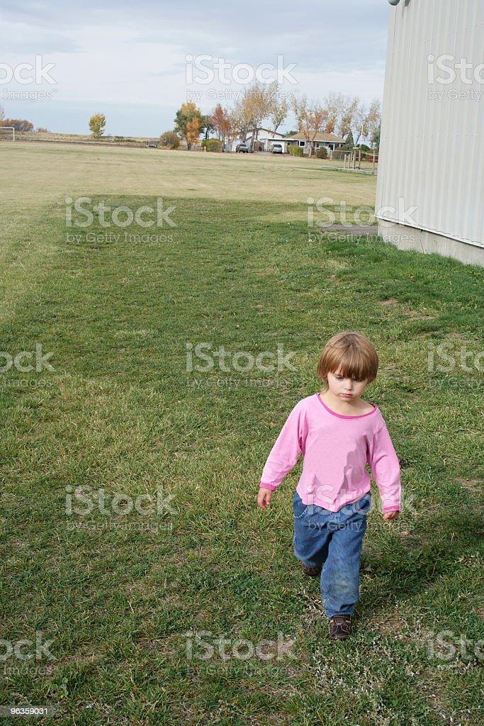 Little girl looks grim as she walks toward camera royalty-free stock photo