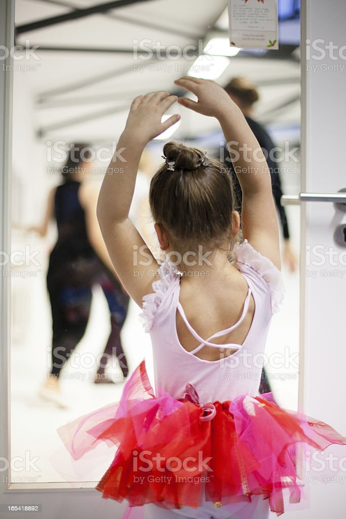 Little girl looks through glass door to the dancers royalty-free stock photo