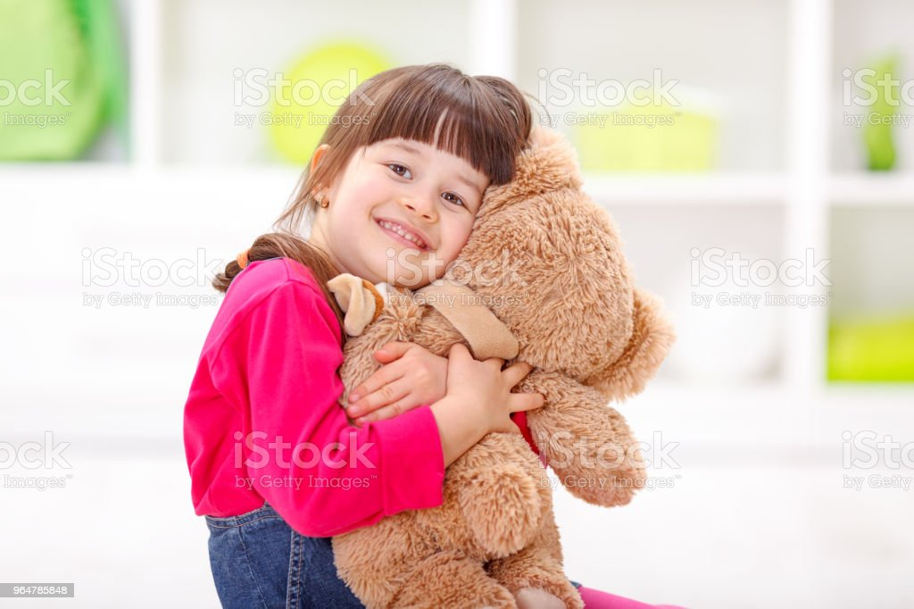 Little girl loving her plush bear royalty-free stock photo