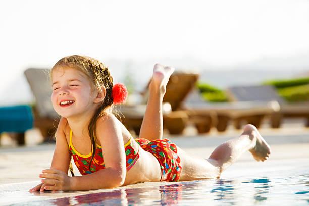 Kleines Mädchen mit Rand des Pools liegen an einem sonnigen Tag – Foto