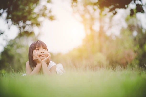 Little girl lying comfortably on the grass and smiling stock photo
