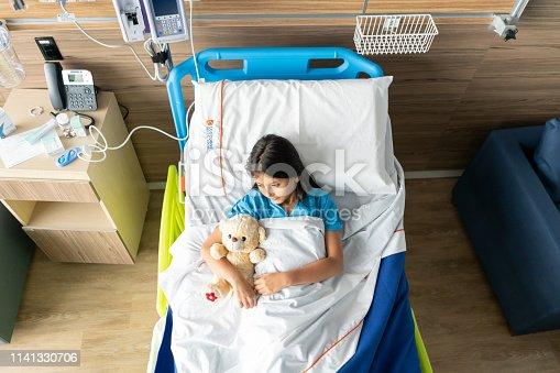 Latin american little girl lying down on hospital bed hugging her teddy bear looking away sad