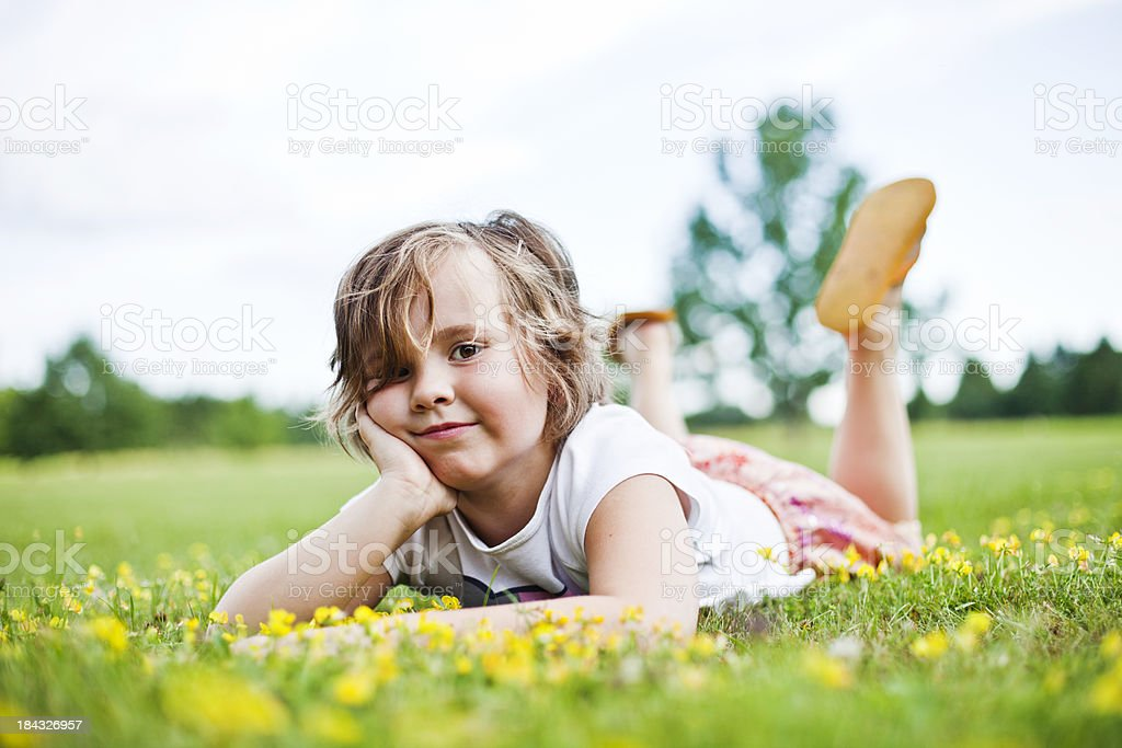 Little girl lying down on the grass royalty-free stock photo
