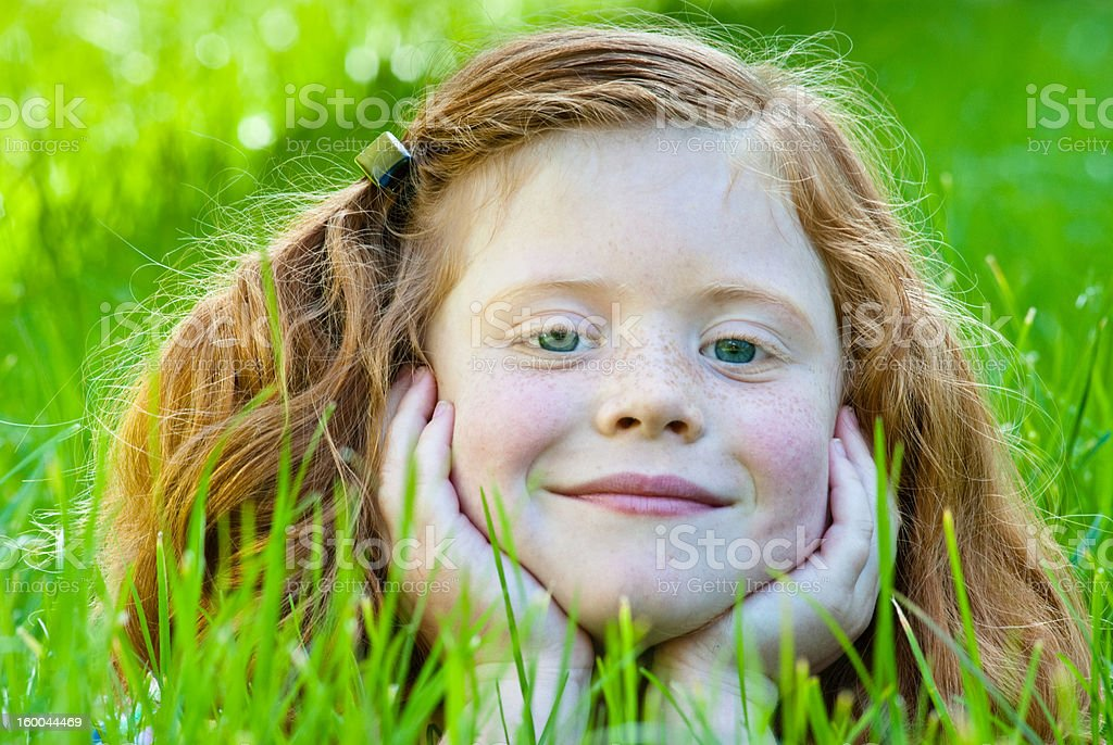 Little girl lying in grass daydreaming royalty-free stock photo