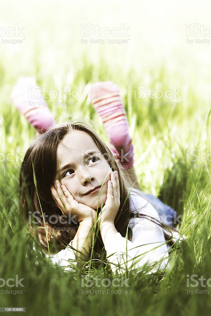 Little Girl Lying in Grass on Sunny Day royalty-free stock photo