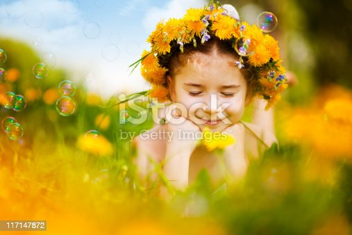 Cute little girl wearing dandelion wreath lying on flower meadow and smiling