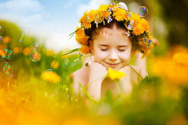 Kleines Mädchen auf dem Bauch liegen Löwenzahn-Feld – Foto