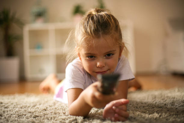 Little girl lying on floor and changing TV channel with remote. stock photo