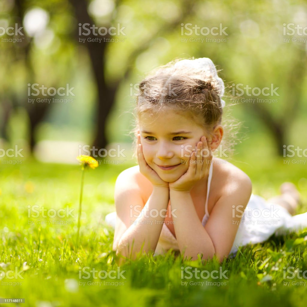 Little girl lying on grass and looking at dandelion flower royalty-free stock photo