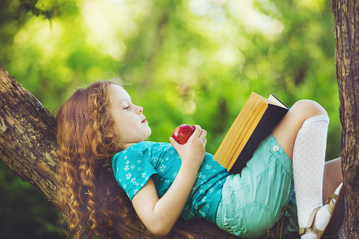 Little girl lying on large tree, eats red apple and reads the book.
