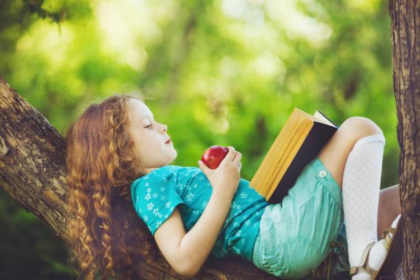 Kleine Mädchen liegend Großbaum, roten Apfel isst und liest das Buch. – Foto