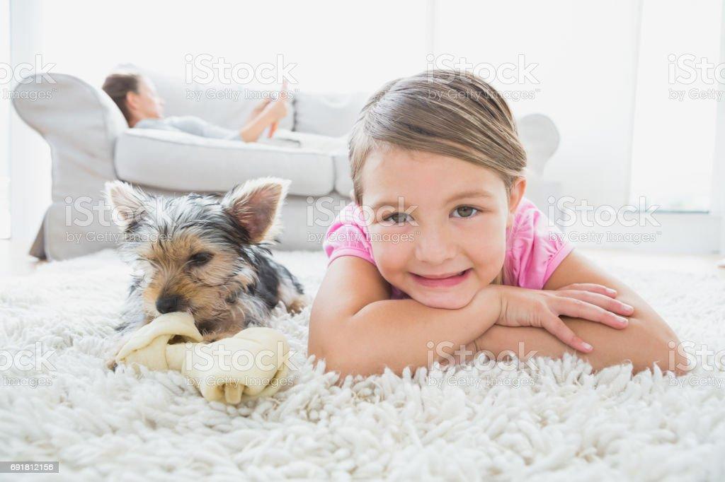 Niña acostada en la alfombra con yorkshire terrier sonriendo a cámara - foto de stock