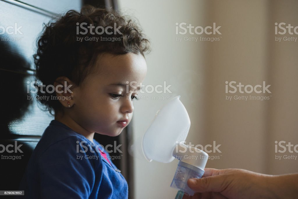 Little girl makes inhalation at home stock photo