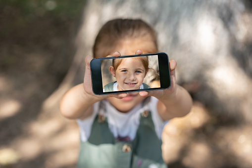 Little girl makes self portrait on smartphone view of screen