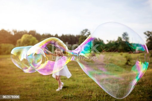 Little girl making a big soap bubble. Focus on the soap bubble. Summer meadow.