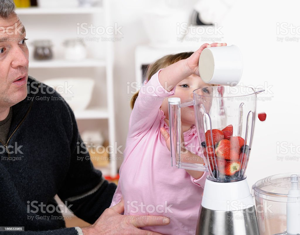 Little Girl Making A Healthy Drink/ Smoothie With Her Father royalty-free stock photo