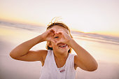 Little girl making a heart with hands at the beach