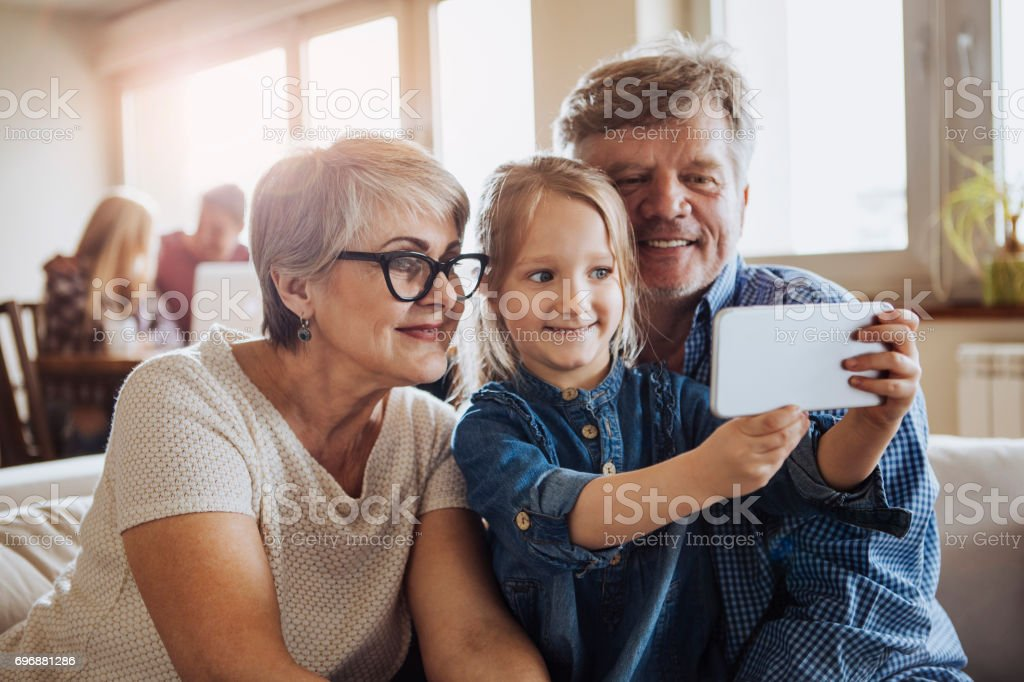 Little girl making a selfie with grandparents stock photo