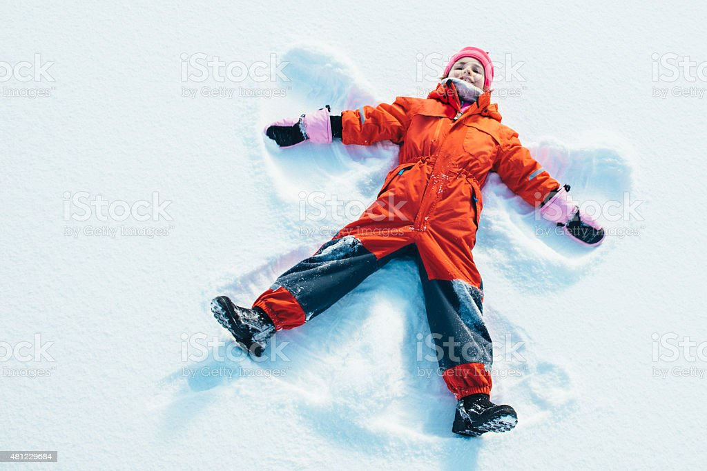 Little Girl making a Snow Angel stock photo