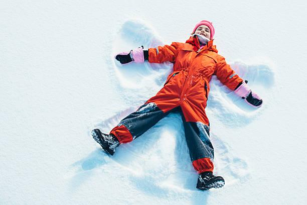 kleines mädchen, einen snow angel - kinder winterstiefel stock-fotos und bilder