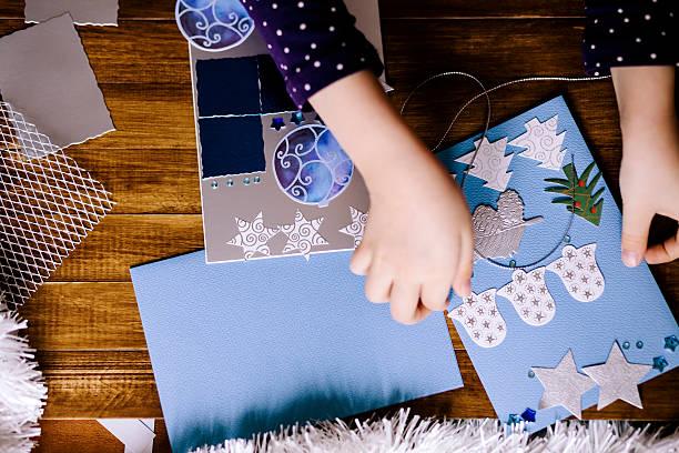 kleines mädchen macht weihnachten karten - weihnachtskarte stock-fotos und bilder