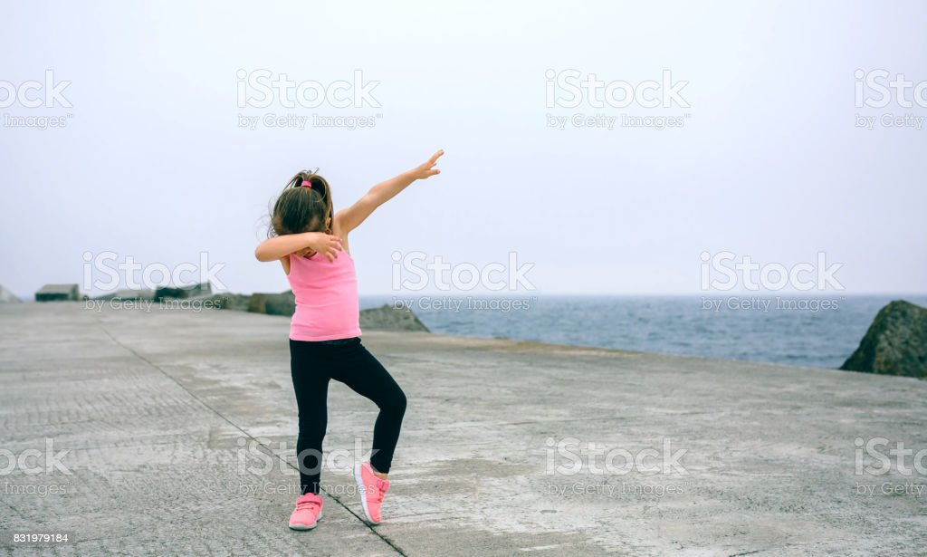 Little girl making dab dance outdoors stock photo